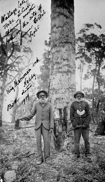 Black and white photograph of two men in front of a marked tree. There is hand written text on the photo including: King Merryman and Neddy. Both dead. 1909.