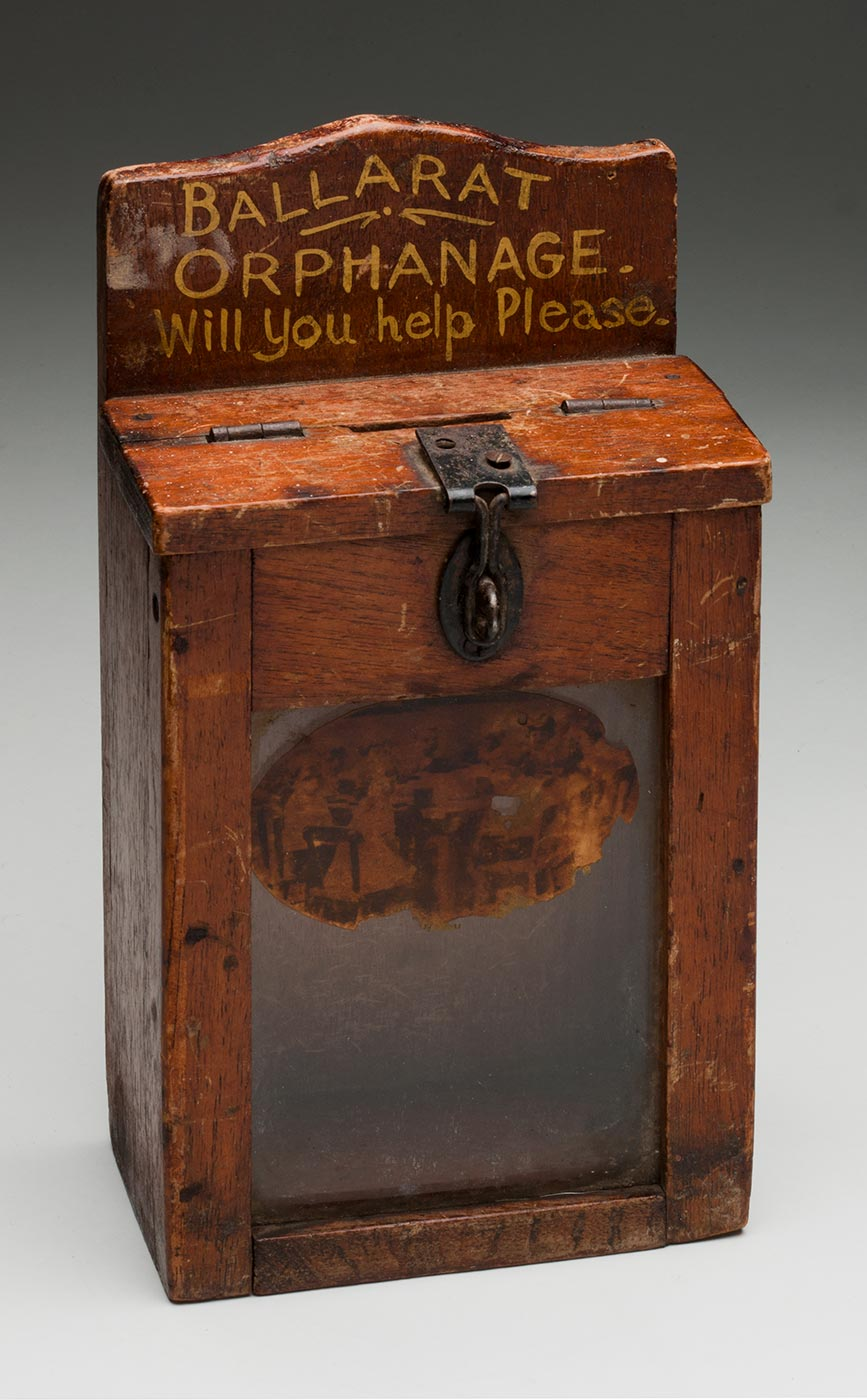 A glass-fronted timber box with the text 'BALLARAT / ORPHANAGE / Will You help Please.' painted in gold at the top. The box has a hinged lid that shuts with a clasp. - click to view larger image