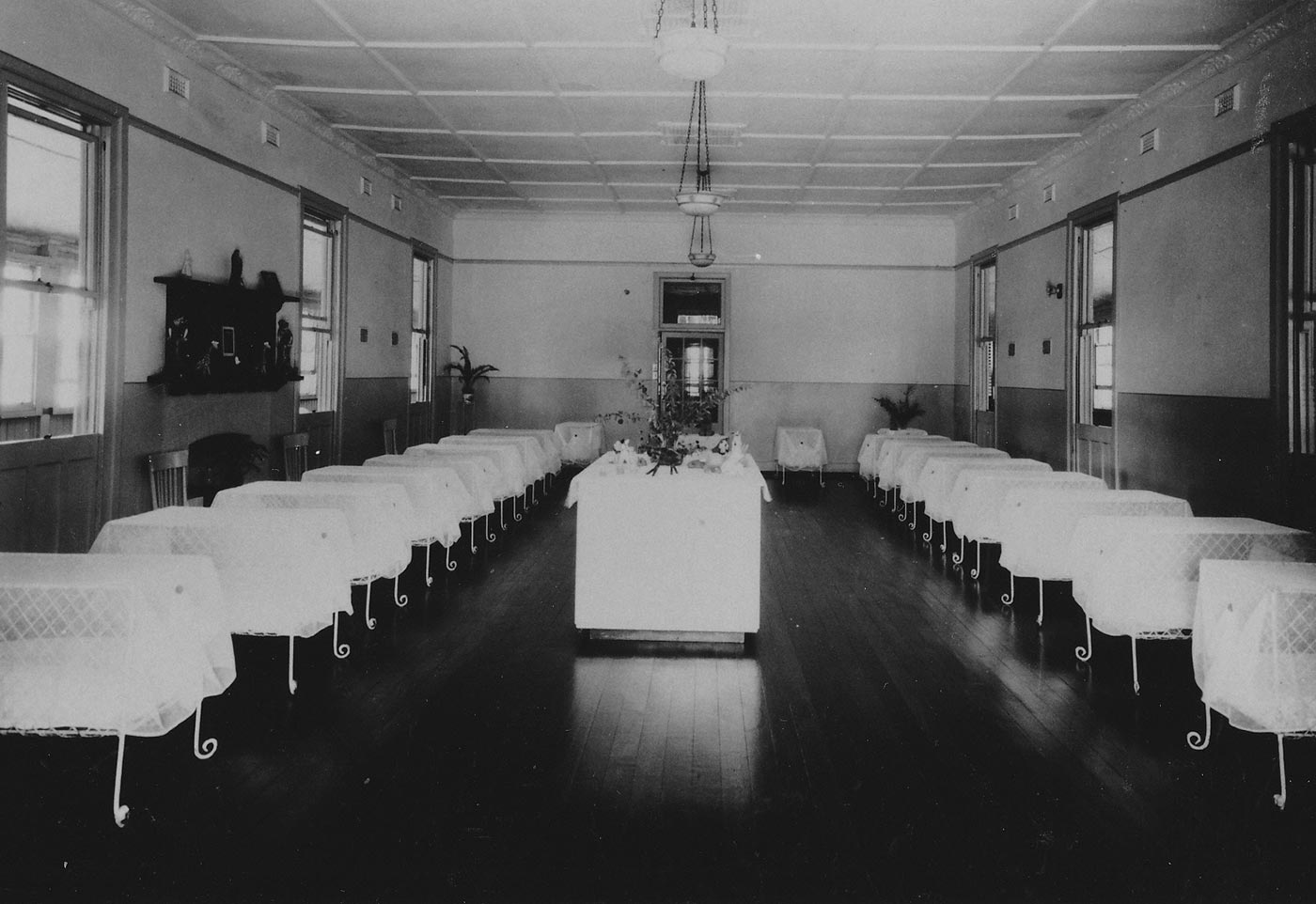 Black and white image showing a large room with two rows of nine white cots on each side. The cots have curved metal feet and are covered with a white, lacy material. At the centre of the room is a large table, covered in white, with a vase of flowers on top. - click to view larger image
