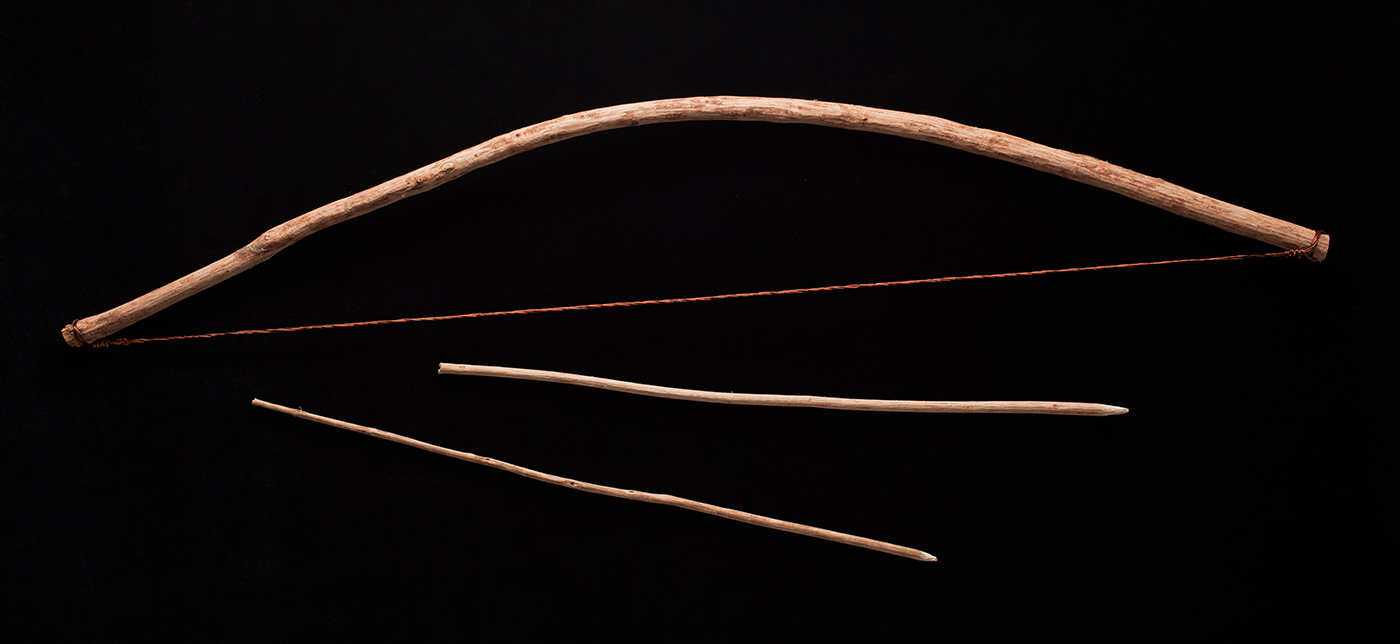 Colour photograph on a black backdrop showing a curved timber bow and two timber arrows. The bow's string is made of copper wire. - click to view larger image