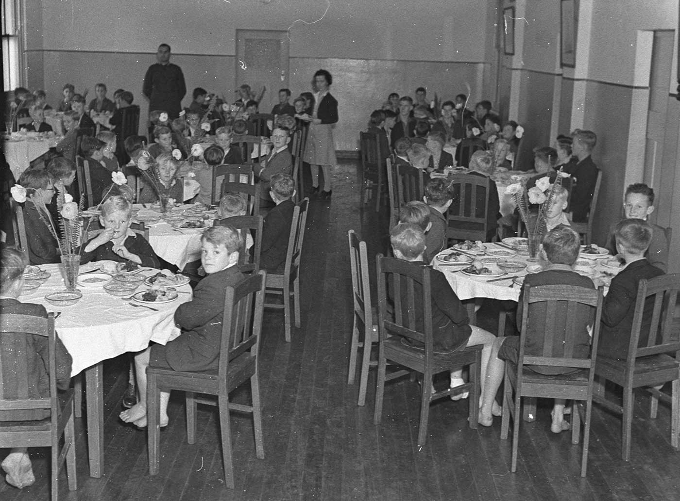 A dining room with numerous groups of young boys seated at round tables. The boys wear coats, shorts and have bare feet. A man and a woman stand at the far end of the room. Each of the tables is set, with a vase of flowers at the centre. - click to view larger image
