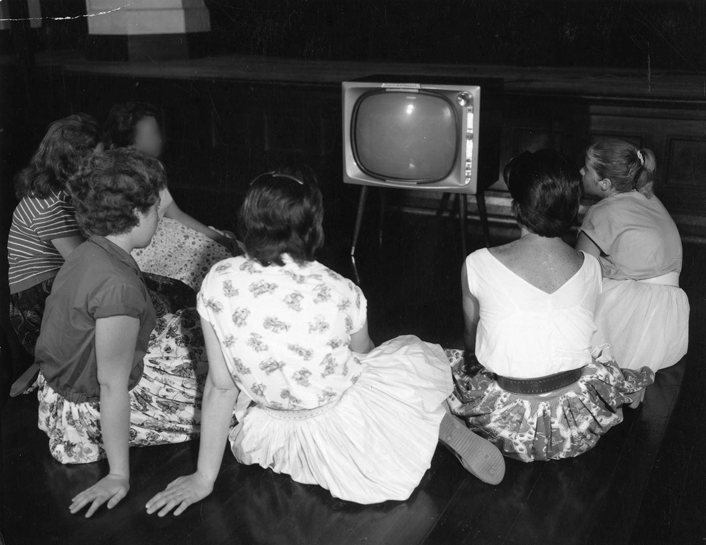 Black and white image showing six teenage girls sitting on the floor, looking at a television. The girls have their backs to the camera. - click to view larger image