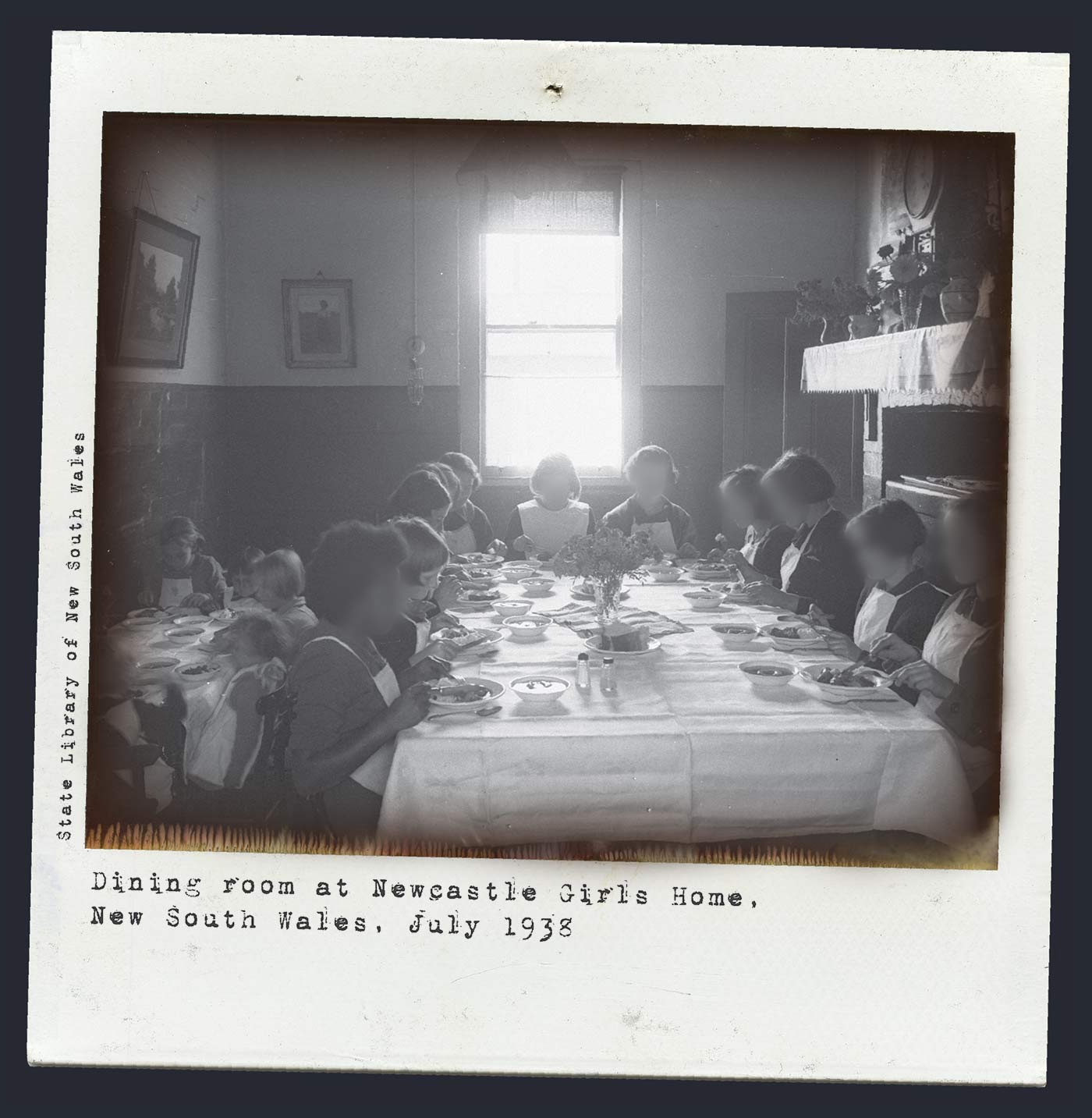 An image of a black and white Polaroid photo of girls sitting around a table eating a meal. Bright light shines through the window at the end of the table. Typewritten text below reads 'Dining room at Newcastle Girls Home, New South Wales, July 1938'. 'State Library of New South Wales' is typed along the left side. - click to view larger image