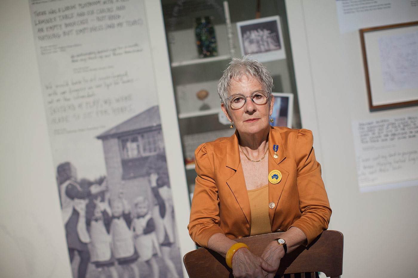 Colour photo showing a woman standing behind a wooden chair in a gallery space, with a large black and white photo and various objects visible on the wall behind. - click to view larger image