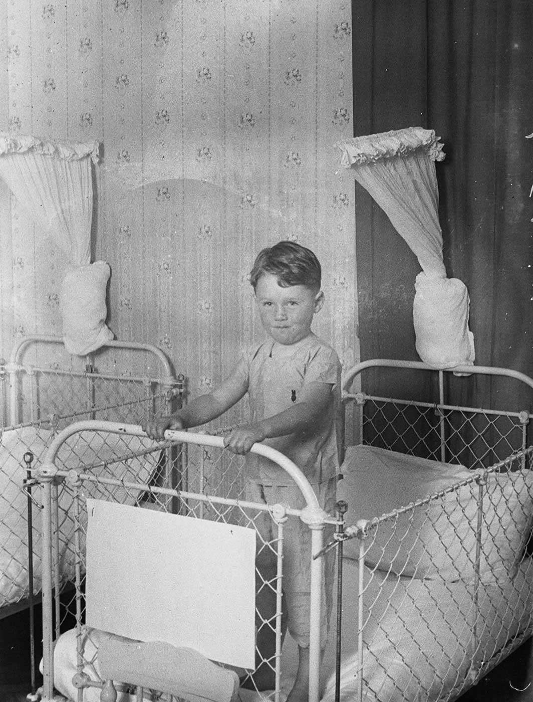 Black and white image showing a small boy standing in a white metal and wire cot. Another cot stands to the left, and in between, on the wall above, white curtains have been tied into a knot. - click to view larger image
