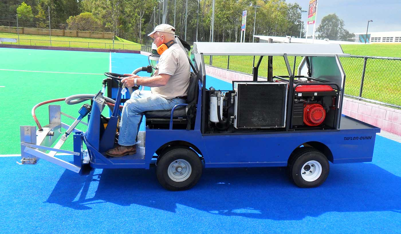 A colour photograph showing a side view of a man sitting on a four-wheeled motorised blue cart. The man steers the cart on a bright blue and green synthetic field surface. - click to view larger image