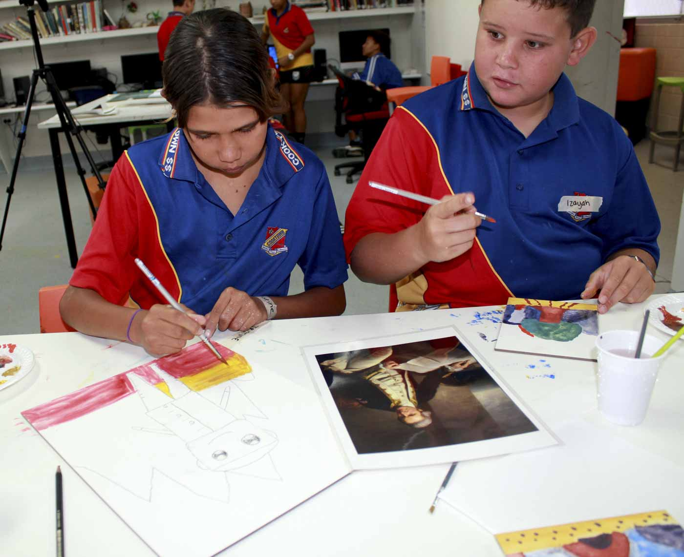 Two primary school students working on paintings of James Cook.. - click to view larger image