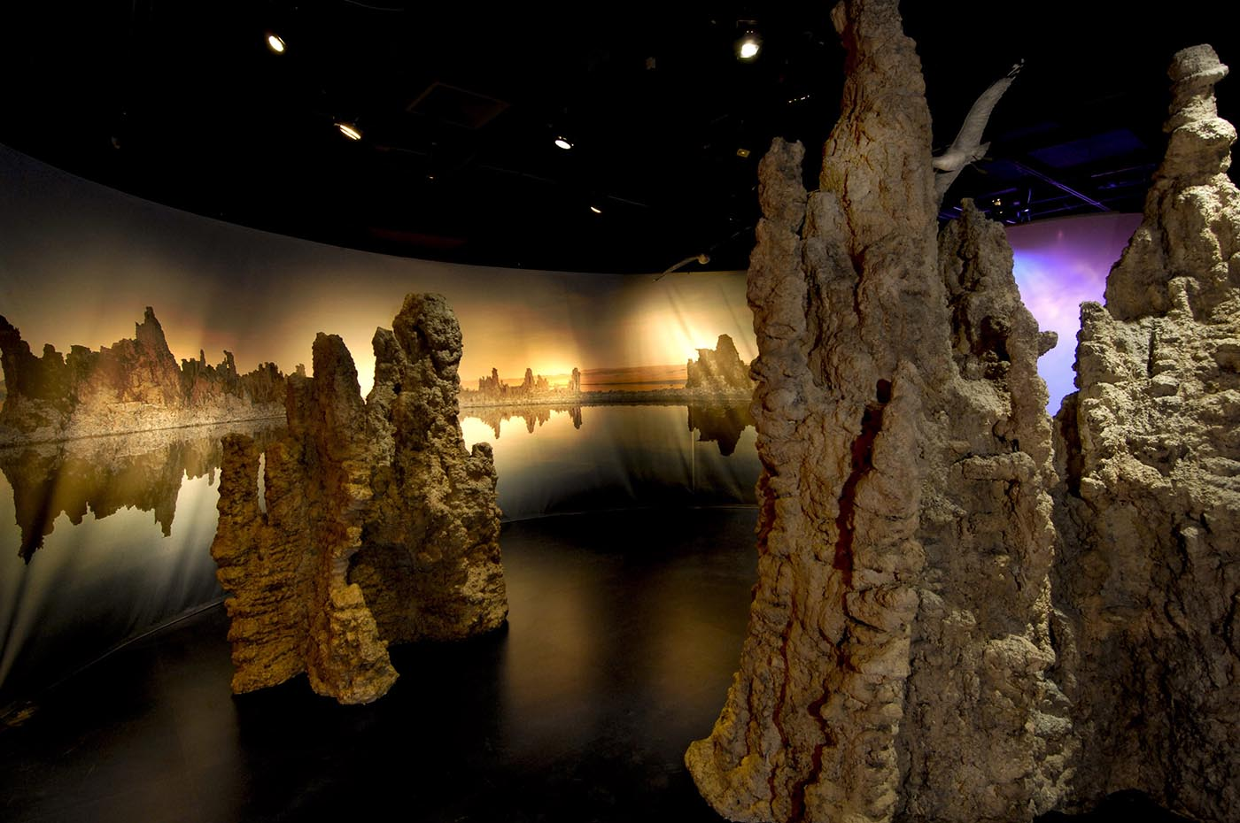 Brown-coloured mineral formations rise in front of panels depicting a lakeside scene.