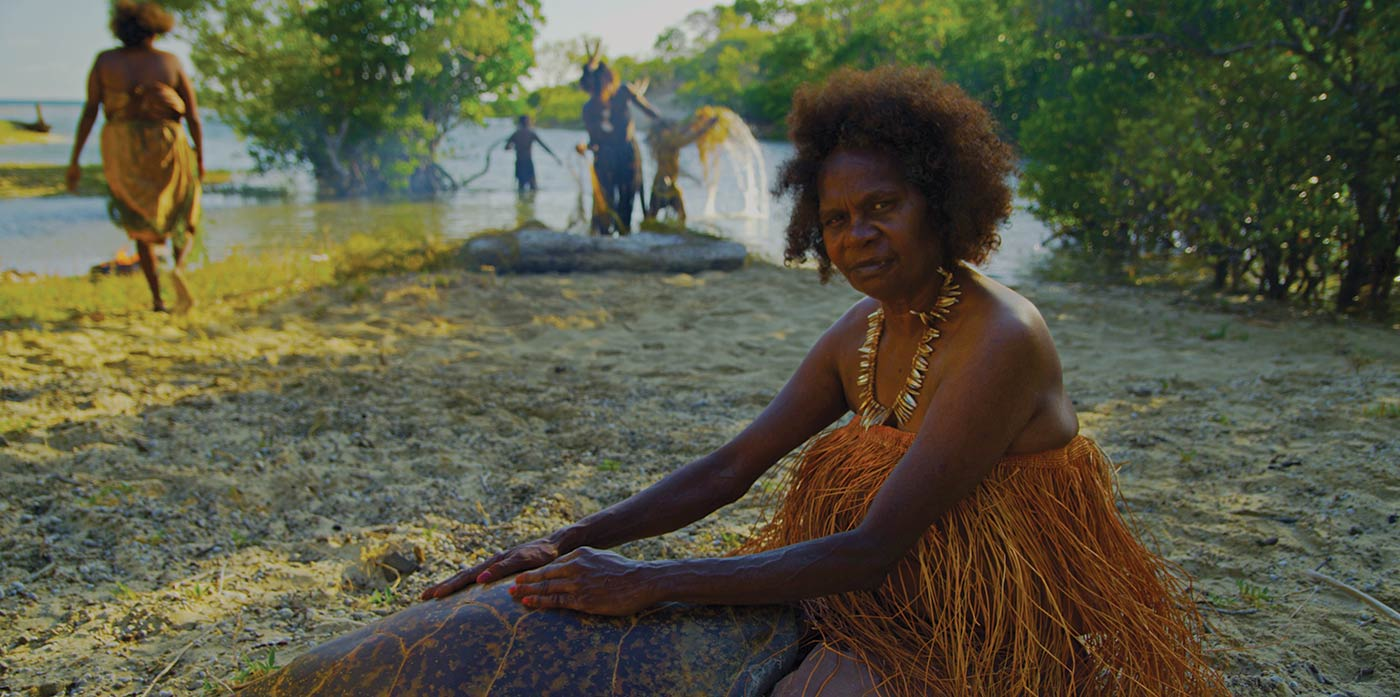 A woman sits on stony sand with her hands placed on a large turtle shell. She is wearing a grass top. There are people in the background working with nets in the shallows.