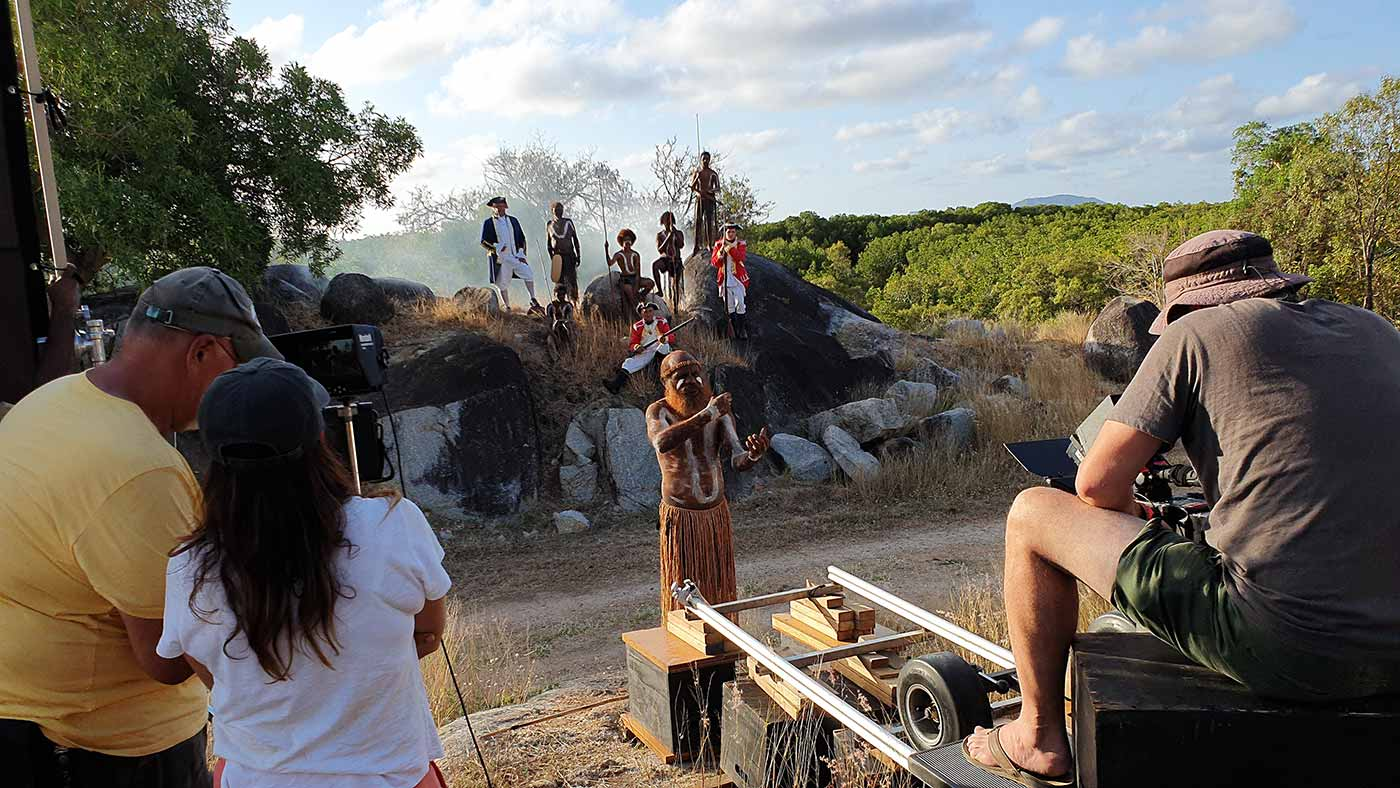 Film set featuring a scene with a ship's captain and soldiers posing on rocks with Indigenous people. The camera focuses on an Indigenous man who stands and gestures with his hands.