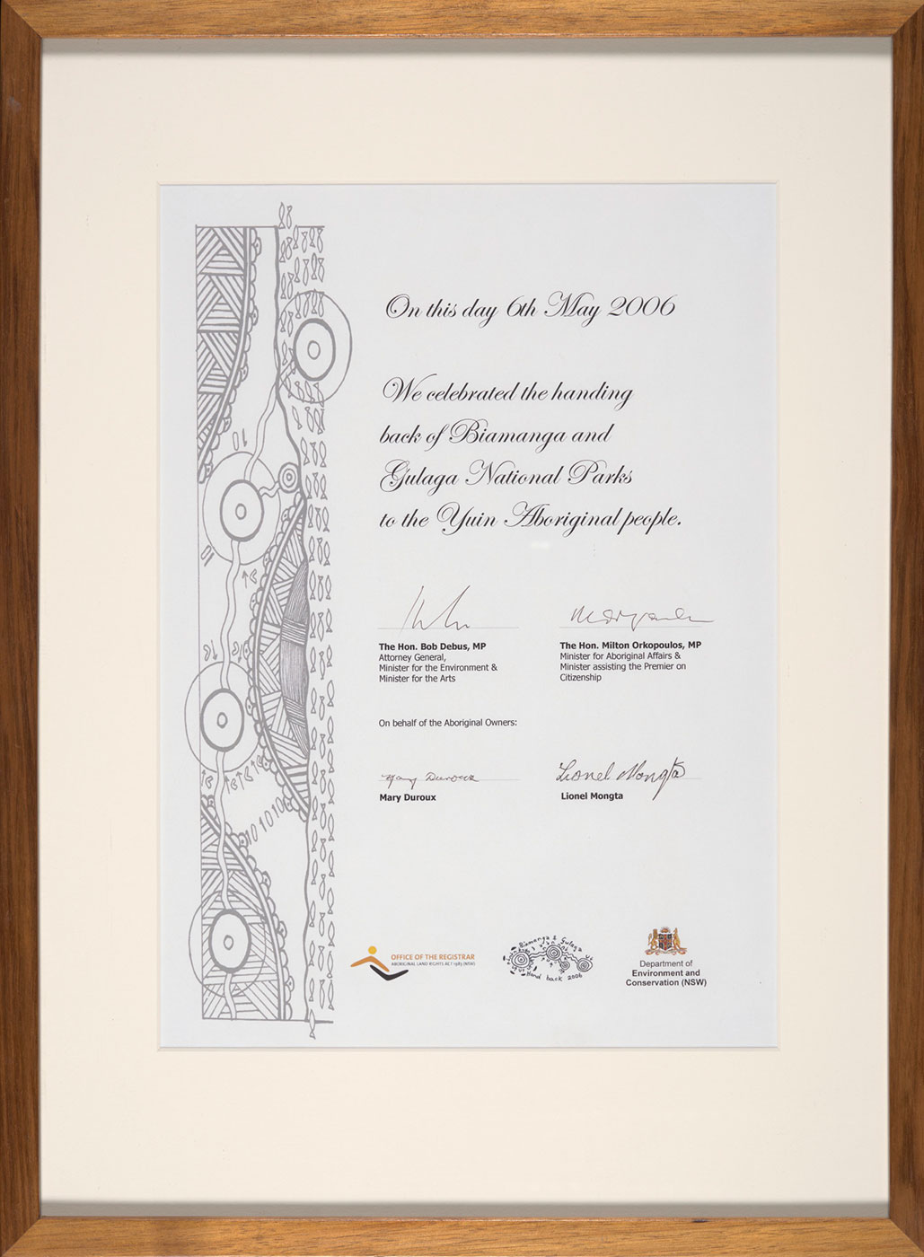 A framed certificate that reads 'On this day 6th May 2006 / We celebrated the handing / back of Biamanga and / Gulaga National Parks / to the Yuin Aboriginal people.' It is signed by 'The Hon. Bob Debus MP', 'The Hon. Milton Orkopoulos, MP', 'Mary Duroux' and 'Lionel Mongta'.