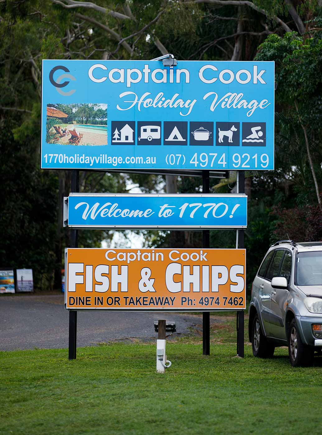 Colour photo of road signage including 'Captain Cook Holiday Village', 'Welcome to 1770!' and 'Captain Cook Fish & Chips'. - click to view larger image