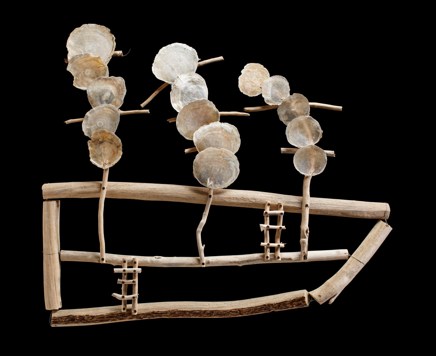 Sculpture of a driftwood boat, with two ladders at the side, and three pearlescent shell sails above. - click to view larger image