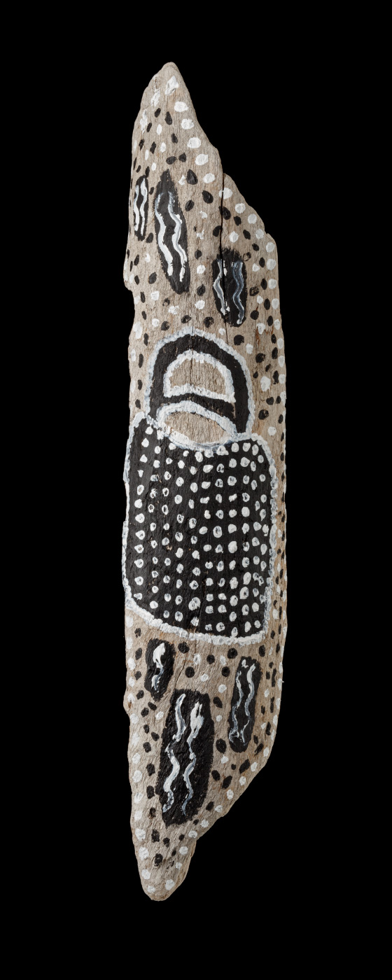 An acrylic painting on driftwood featuring a black bag outlined with white dots and filled with white dots. The bag is surrounded with black and white dots, and black thick vertical painted strokes with white vertical wave lines within them. - click to view larger image