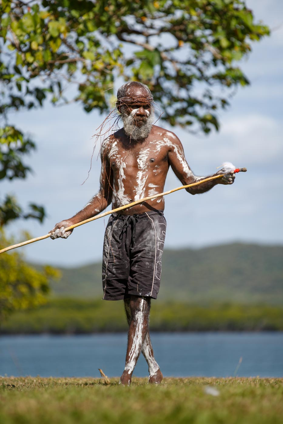 Colour photo of a man in costume and holding a spear as part of an outdoor festival. - click to view larger image