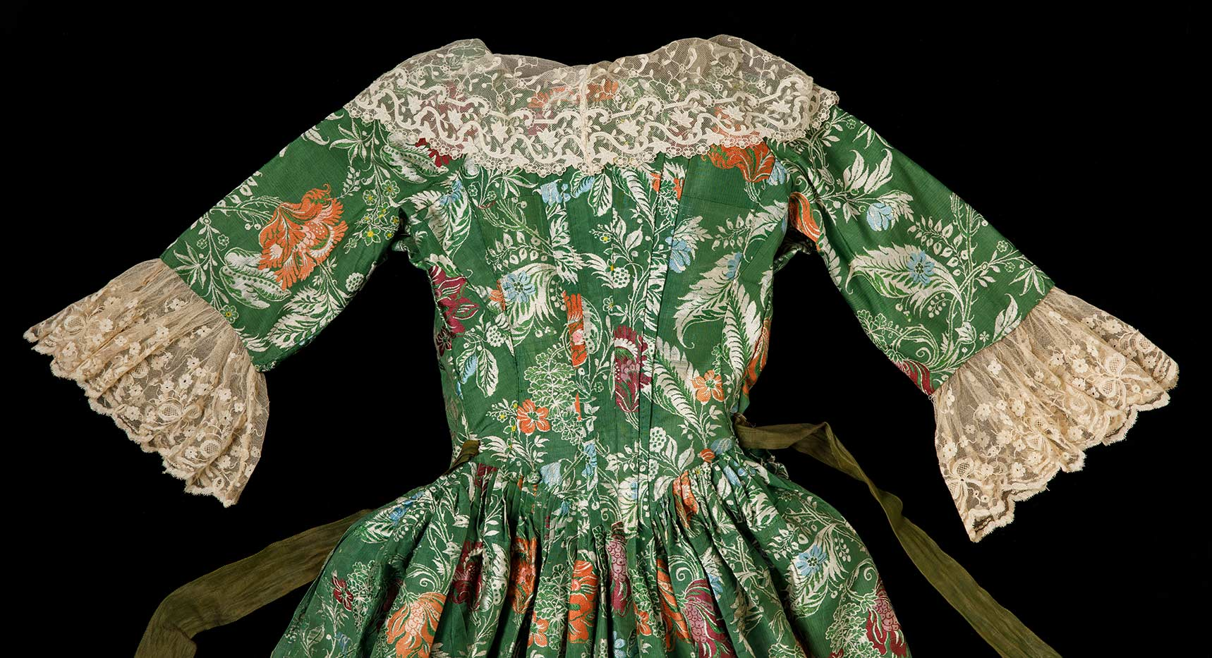 A detail image of the top part of the back of a green and floral dress with lace trim on the sleeves and collar with a long green sash like belt stitched at the waist. - click to view larger image
