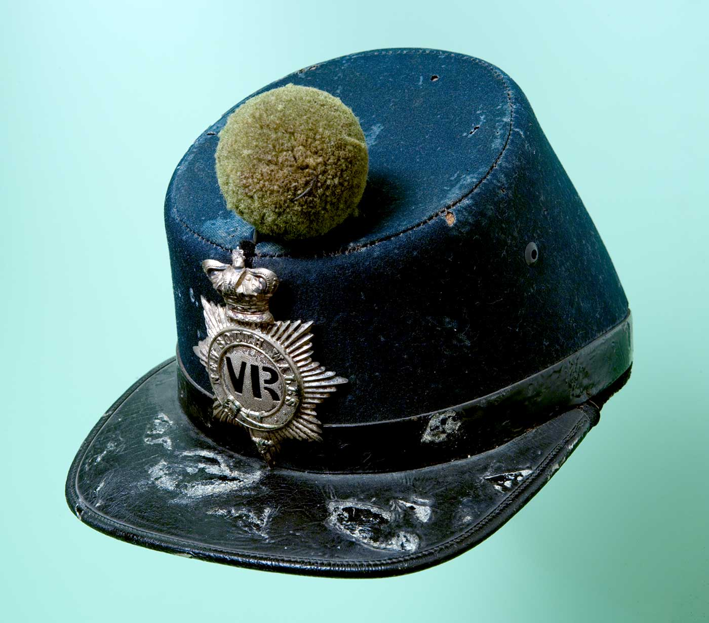 Dark blue hard cap with VR silver emblem in front and above a leather brim in the front and perched on top is a woollen pompom. - click to view larger image