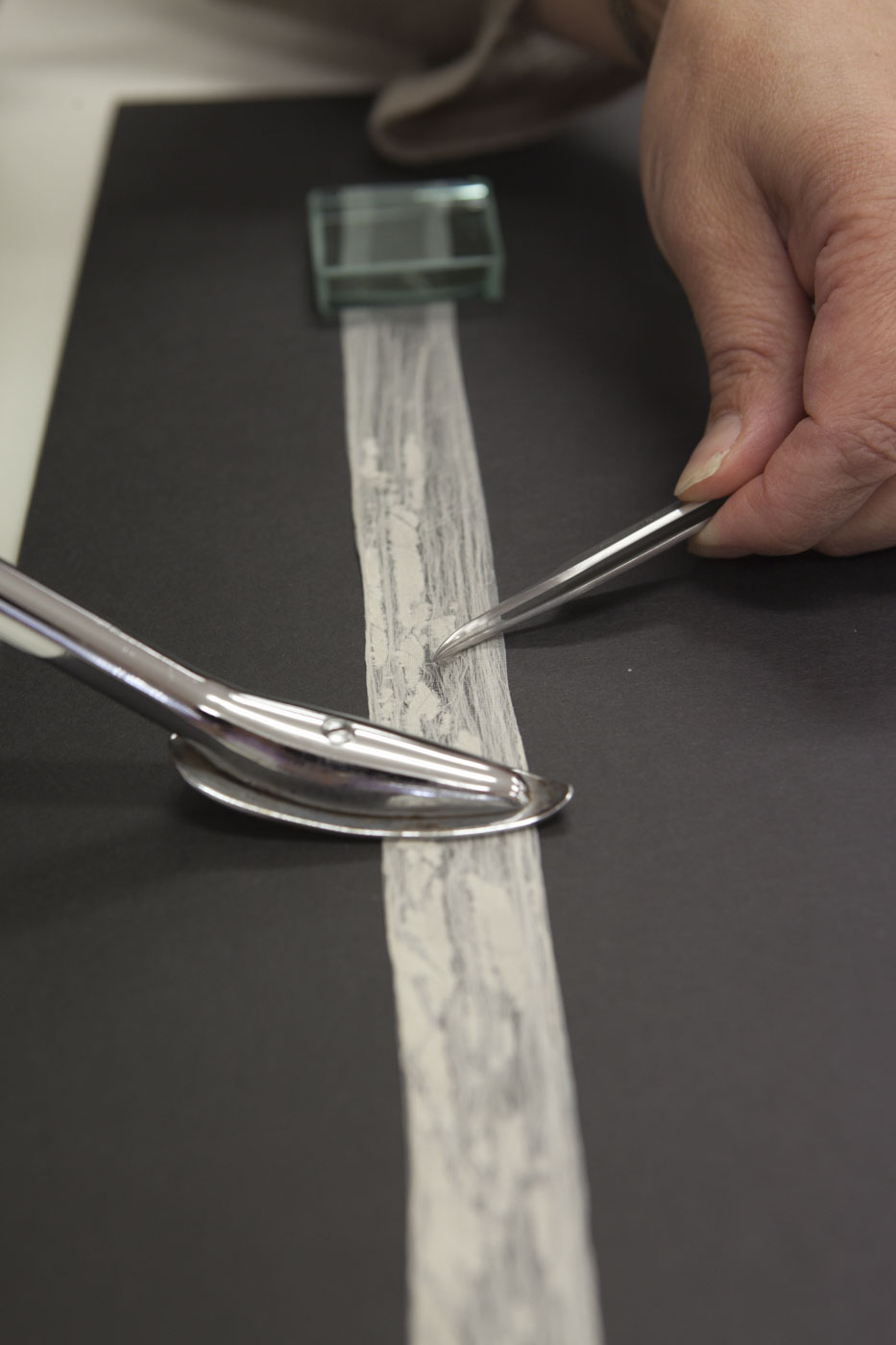Conservator using tools for delicate lace strip. - click to view larger image