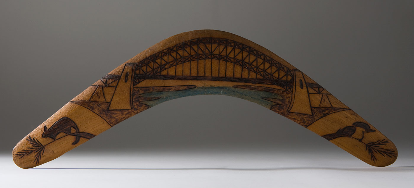 Boomerang made of light-coloured wood, depicting the Sydney Harbour Bridge in the centre, with a possum to its left and a kookaburra to its right.