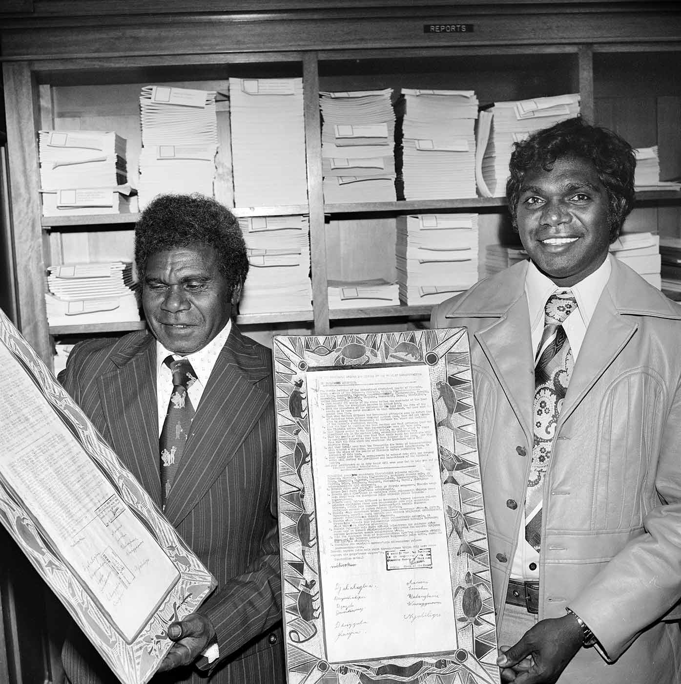 Black and white photo of two men in business suits in an office smiling for the camera. They are holding up panels of bark featuring detailed artwork framing official printed documents with stamps and signatures.