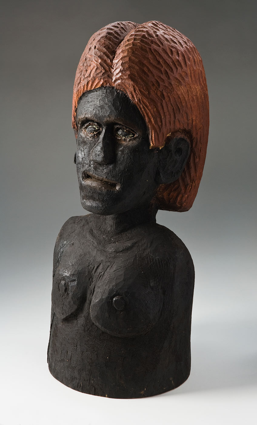 A carving of a nude female torso made from a solid piece of cylindrical wood and pigmented. Most of the carving is coloured black with the facial and chest features carved lightly in relief. The eyes have an outline of cream paint and the nose is flattened. The shoulder length hair is coloured orange brown, and is covered with short vertical grooves. - click to view larger image