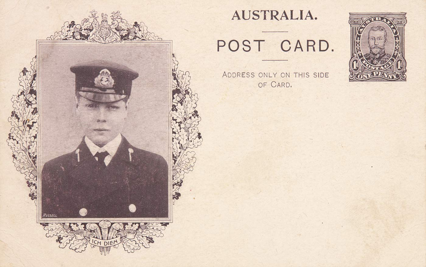 A postcard featuring a black and white portrait of a young man's face. He is wearing a cap with a crest on it and a dark military jacket with a white shirt and a dark tie. The image is located on the left side of the postcard and is surrounded by an oval wreath of oak leaves. The words