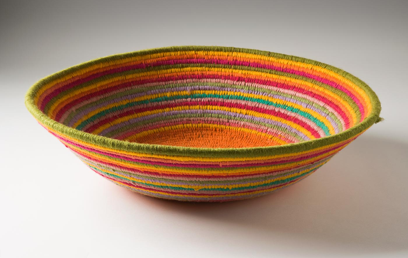 A multi-coloured circular coiled bowl-shaped basket made of yarn and plant fibre. The centre of the basket is in orange yarn which persists out to where the edges start to turn up. The rest of the basket is in horizontal stripes of yellow, dark pink, light pink, lime green and lavender yarn. - click to view larger image