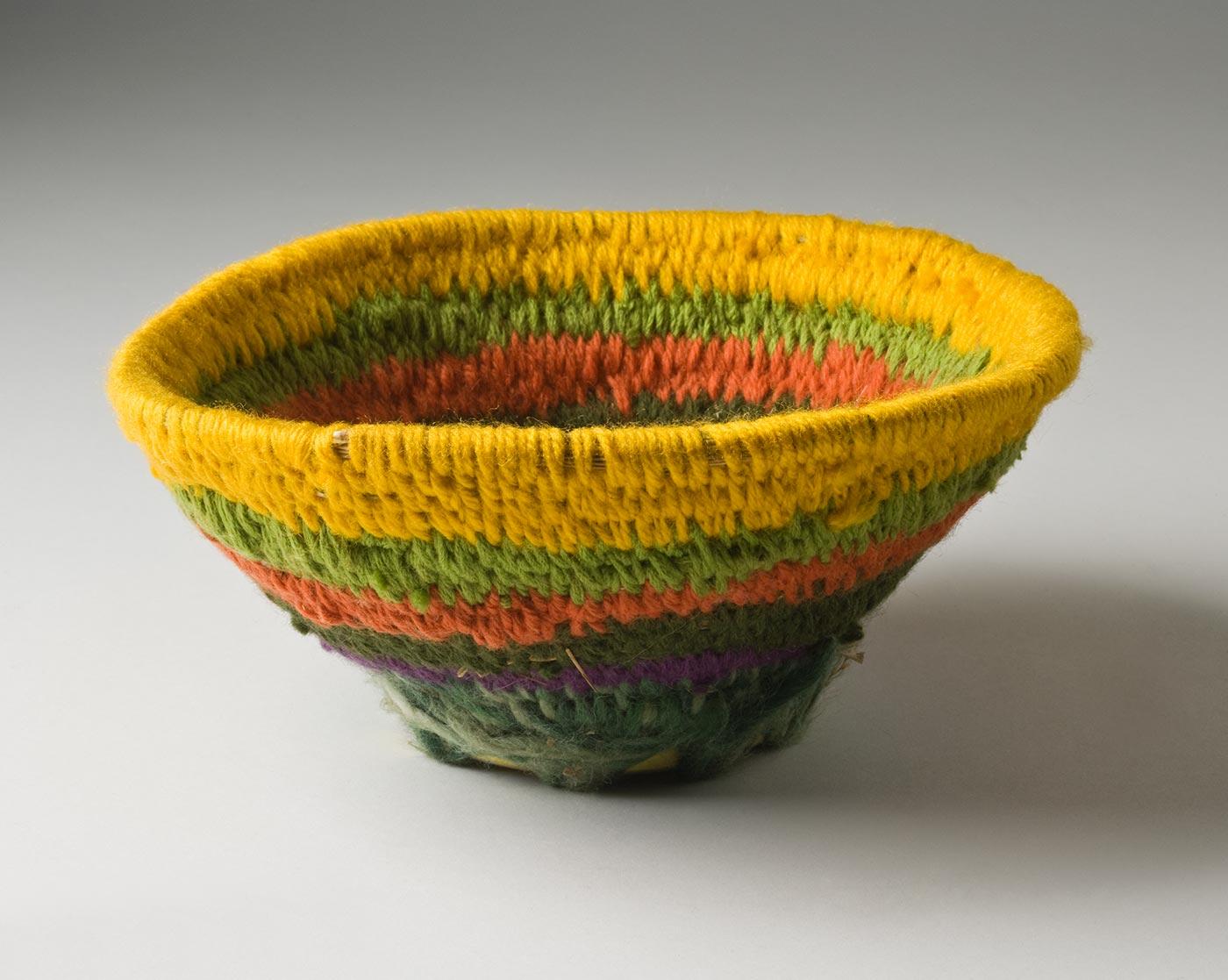 A circular coiled striped yarn basket over plant fibre, with a metal base. The basket has a circular tobacco tin base with text on the back and holes punched around the base. The yarn coiled fibre section is attached with yarn through the holes in the tin, and opens out toward the top. The basket has a stripe of yellow at the top edge followed by green, orange, dark green, purple and white-green. - click to view larger image