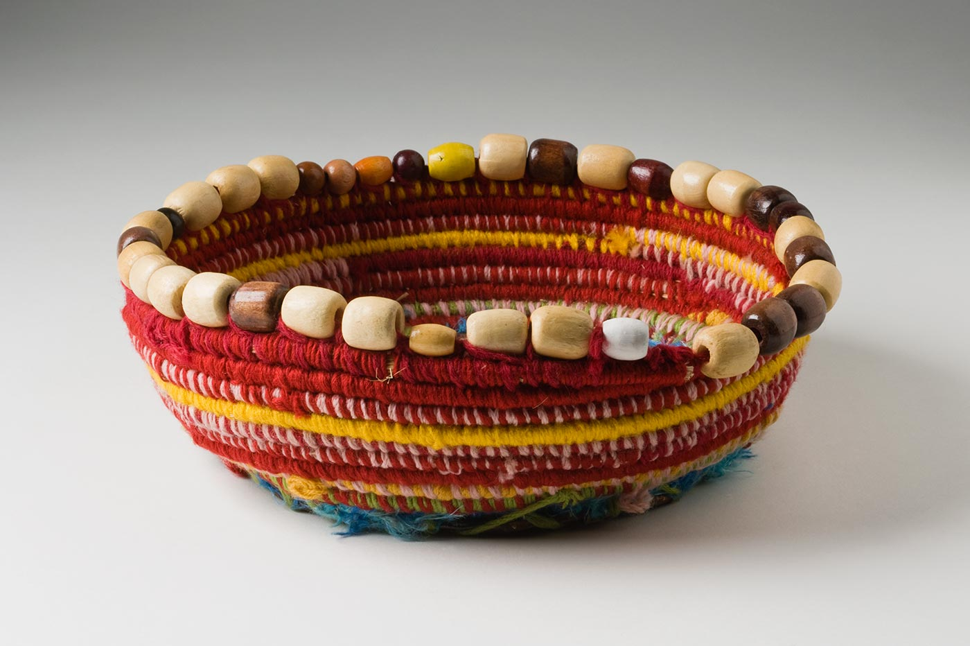 A shallow circular coiled red toned yarn and plant fibre basket with a metal base and bead trim. The base is made of a