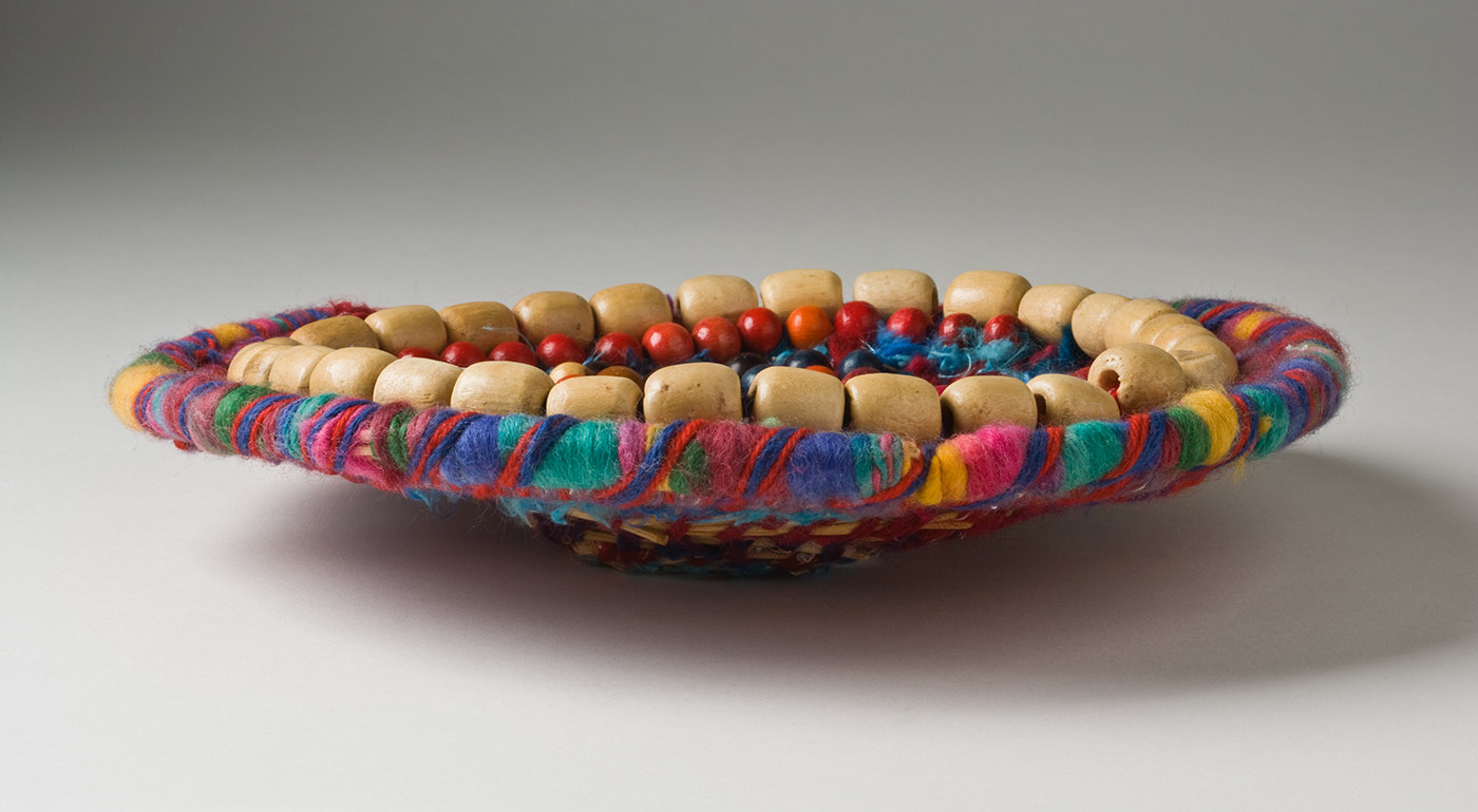 A shallow multicoloured coiled yarn over plant fibre basket decorated with circles of beads. The yarn is in rainbow colours with a dark pink most dominant. Some of the yarn has small sequins on it and one of the yarns is a fluffy blue and aqua. There is a circle of natural wood cylinder beads near the edge of the basket, with rows of natural coloured oval wood beads and multicoloured round wood beads inside it. The centre of the basket is teal green yarn with maroon yarn over it, which then changes to fluffy blue yarn for one round. After this blue row the basket has a number of rows where the coiled yarn is spaced out showing the fibre underneath. - click to view larger image