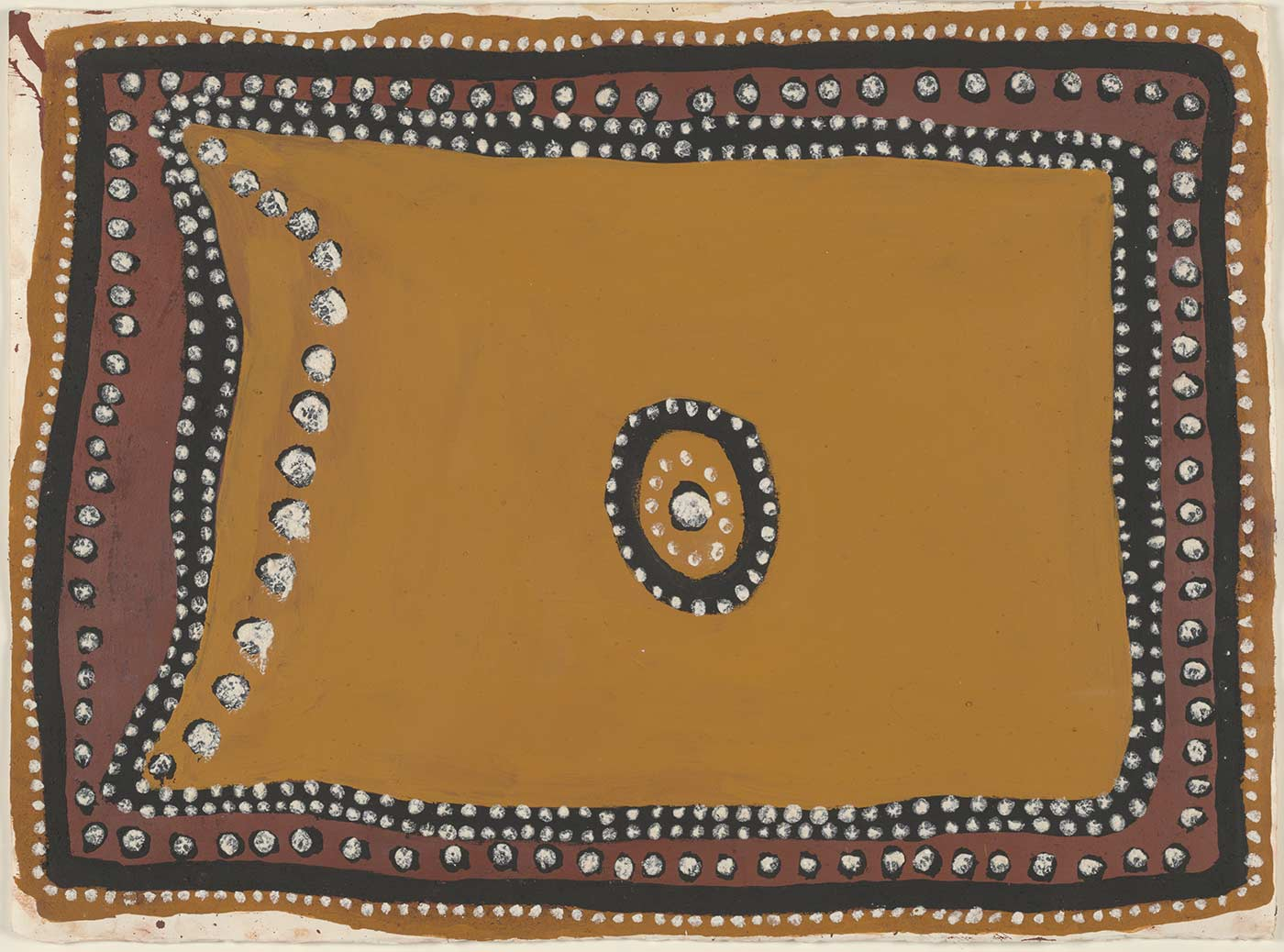 A painting on heavy mat paper. It appears to be painted in ochre and features ochre yellow as the main background colour with a black and red border that has white dots on it. The centre of the painting shows a black circle with white dots around it. Inside the black circle is another ring of white dots and at the very centre is one large black dot with a white dot on top of it. The left hand side of the painting shows a curved vertical line of large black dots with large white dots over them.