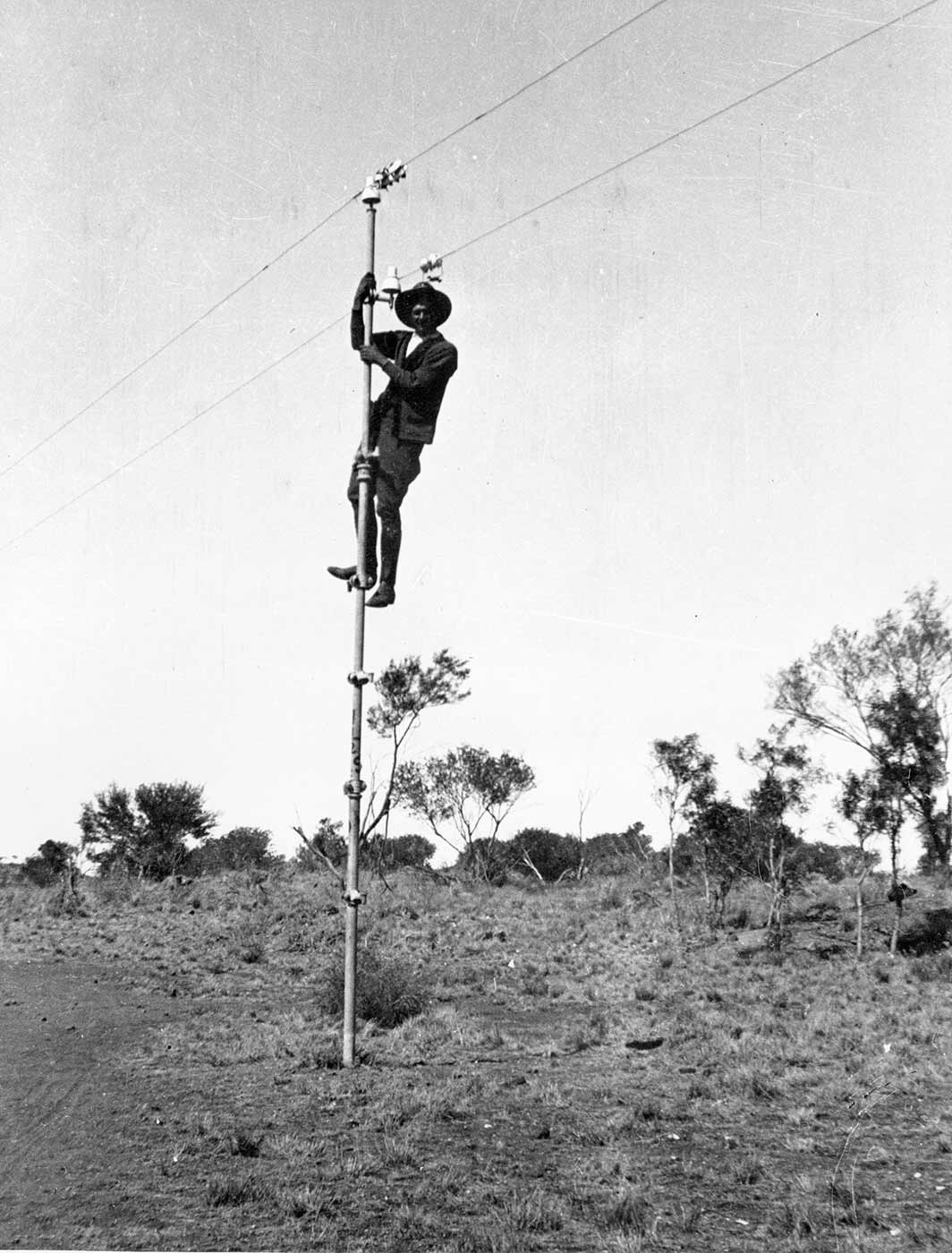 A black and white photo taken in the 1920s of a man who has climbed up to the top of a pole. - click to view larger image