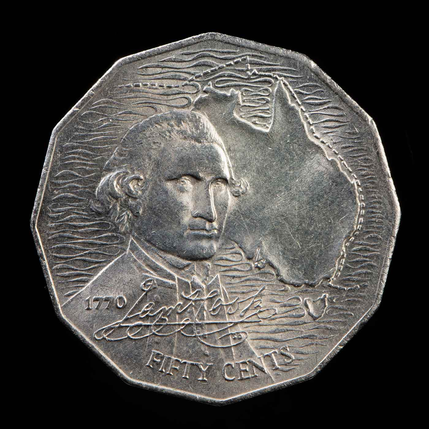 An Australian 50 cent coin with a picture of the map of Australia and the bust of Captain James Cook. The text '1770' then his signature and 'FIFTY CENTS' is located over the lower half of the bust. - click to view larger image