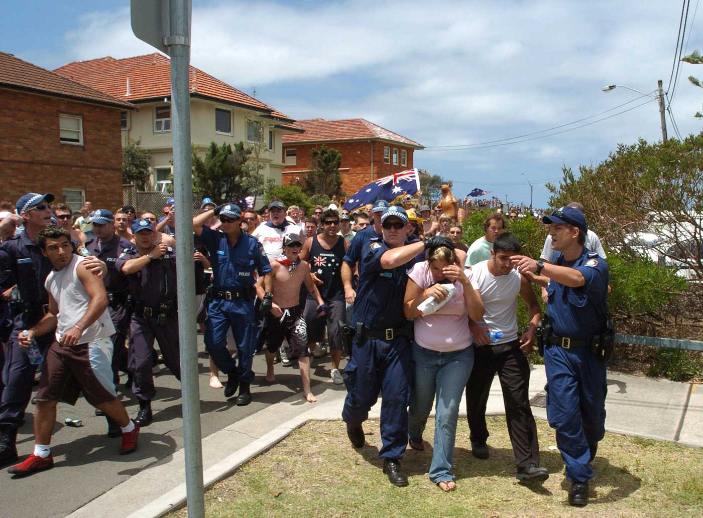 Young people being protected by police from a riot of predominantly white male protesters with the Australian flag.