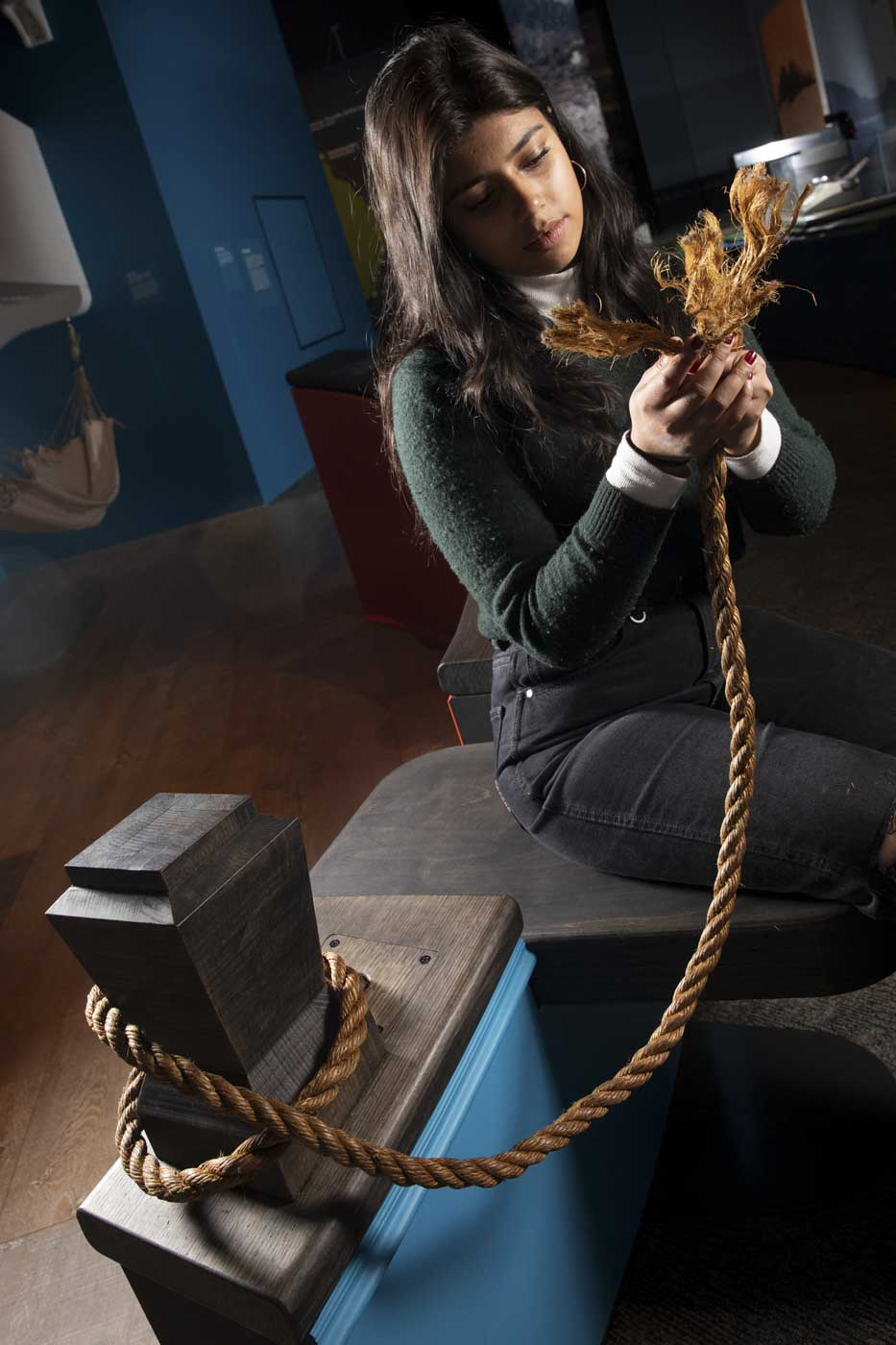 A woman sits in an exhibition space, holding a thick rope in front of her. The rope is unspliced at the end. - click to view larger image
