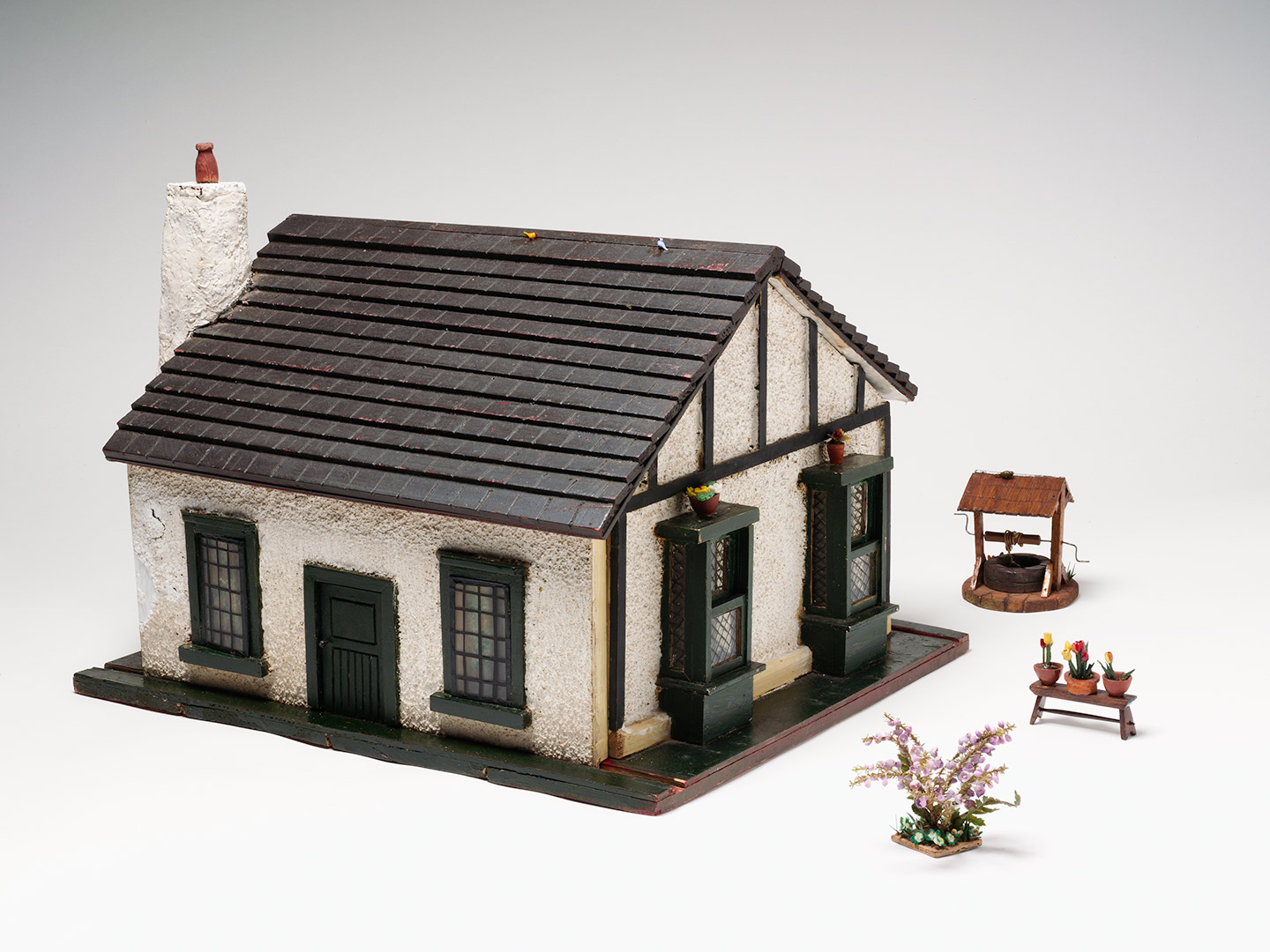 Doll's house and accessories, standing on a base board. Hinged roof section, exterior walls decorated with a white plaster pebble-effect finish and a dark tile-effect roof.