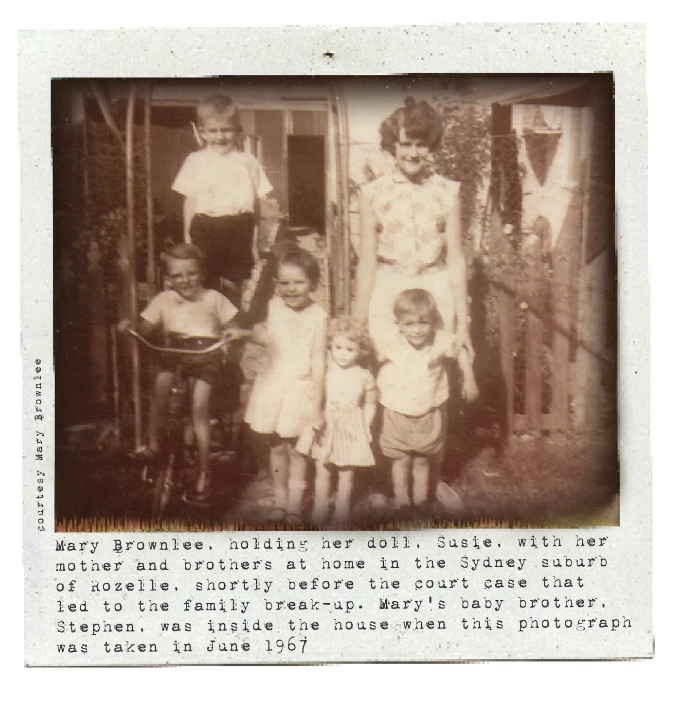 Black and white Polaroid photograph showing a young woman with three small boys and a small girl outside a house. They are positioned in a group facing the camera and all smiling. One the boys is sitting on a tricycle and the girl is holding a large doll. Typewritten text underneath reads: 'Mary Brownlee, holding her doll, Susie, with her mother and brothers at home in the Sydney suburb of Rozelle, shortly before the court case that led to their family break-up. Mary's baby brother, Stephen, was inside the house when this photograph was taken in June 1967'. In smaller text, on the left-hand side of the image, in a vertical direction, reads: 'Courtesy Mary Brownlee'. - click to view larger image