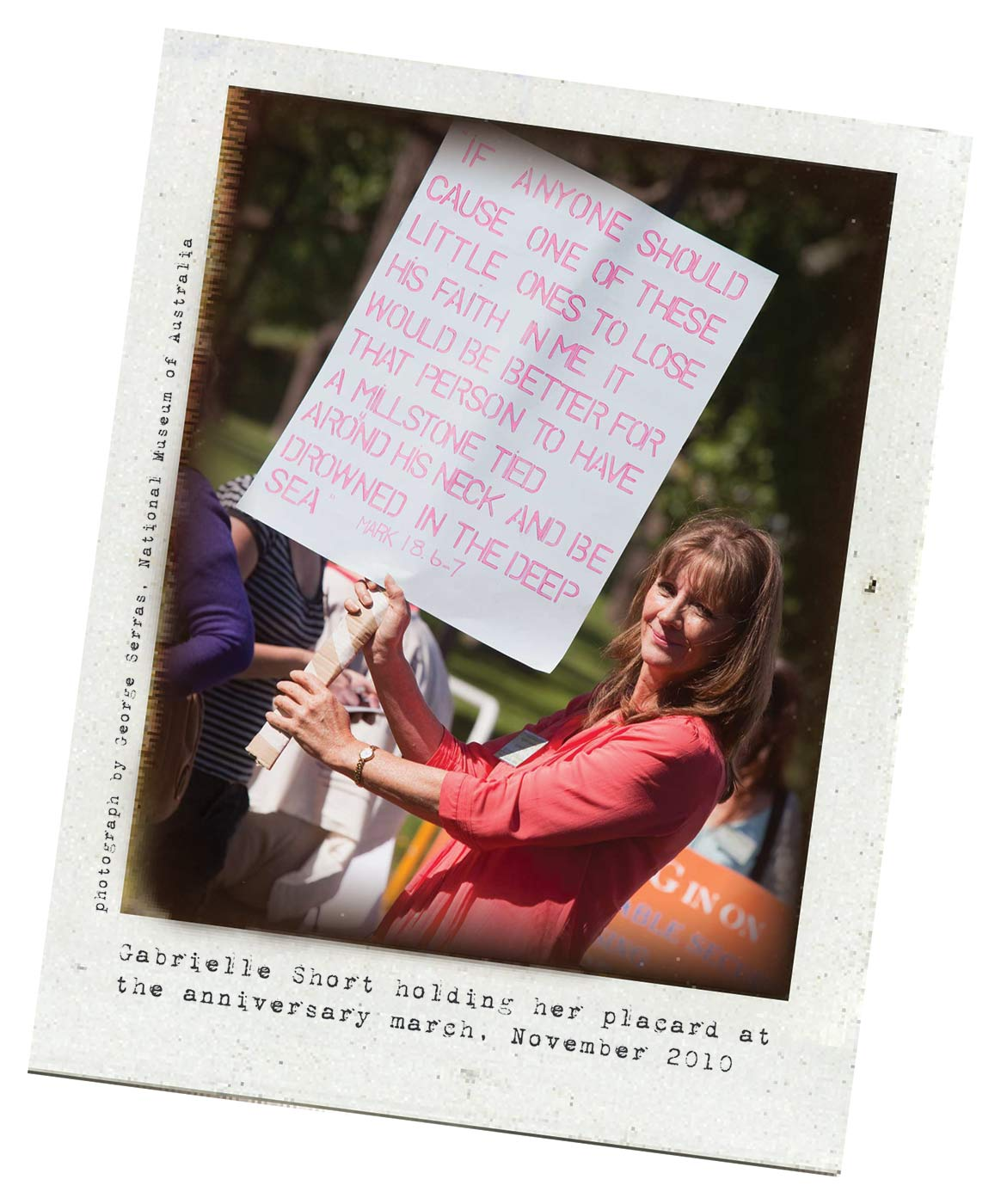 A Polaroid photo of a woman holding a banner on a white cardboard sheet. Typewritten text below reads 'Gabrielle Short holding her placard at the anniversary march, November 2010.' 'Photograph by George Serras, National Museum of Australia' is printed along the left side. - click to view larger image