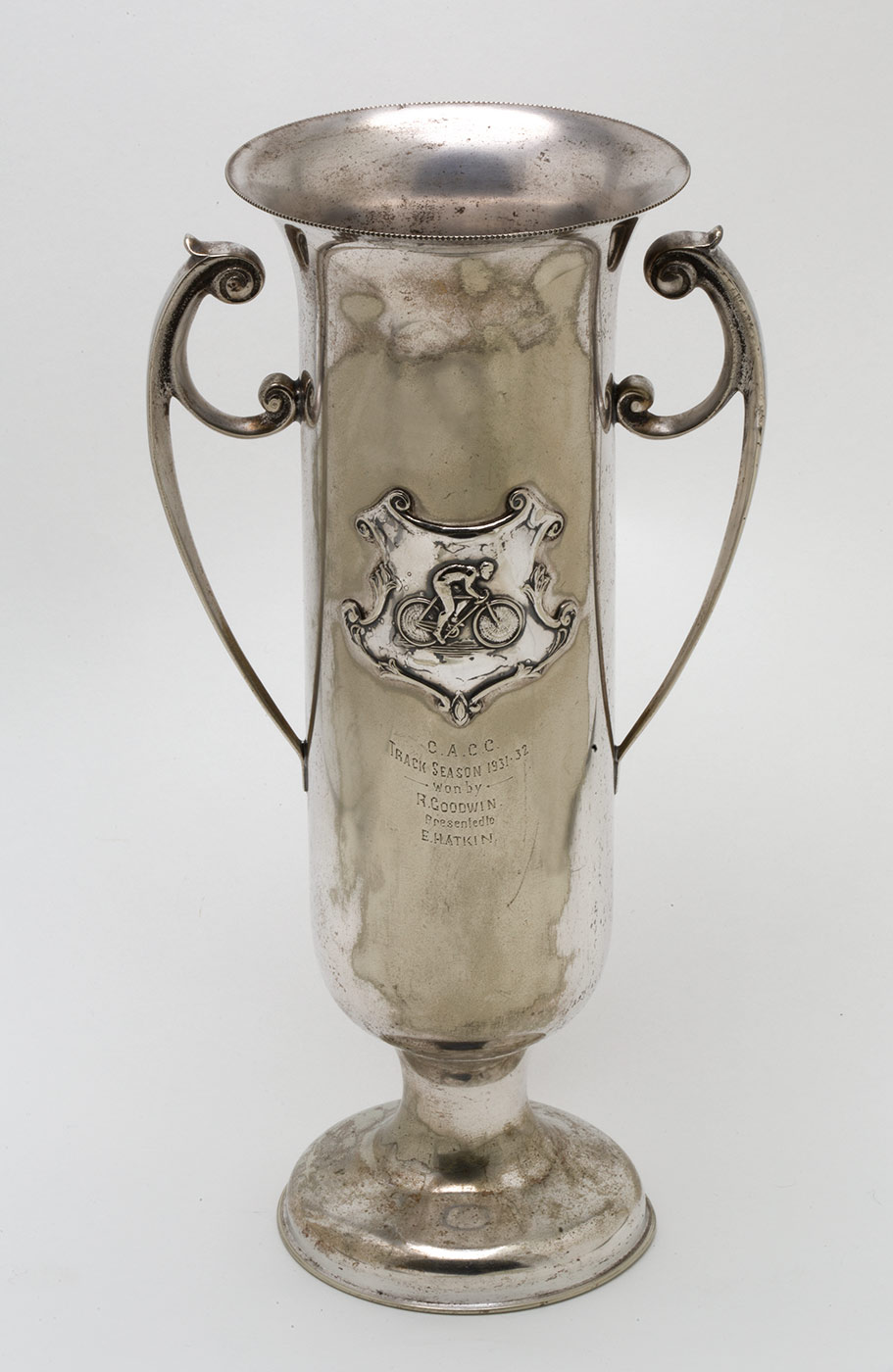 A two handled silver presentation cup with a decorative shield featuring a raised relief of a cyclist. Below the shield is engraved inscriptions that read 'C.A.C.C. / TRACK SEASON 1931-32 / WON BY / R. GOODWIN / PRESENTED TO / E. WATKIN.'. - click to view larger image