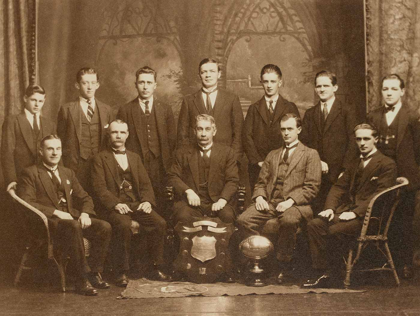 Members of the Footscray Rainbow Cycling Club with club trophy, 1925. - click to view larger image