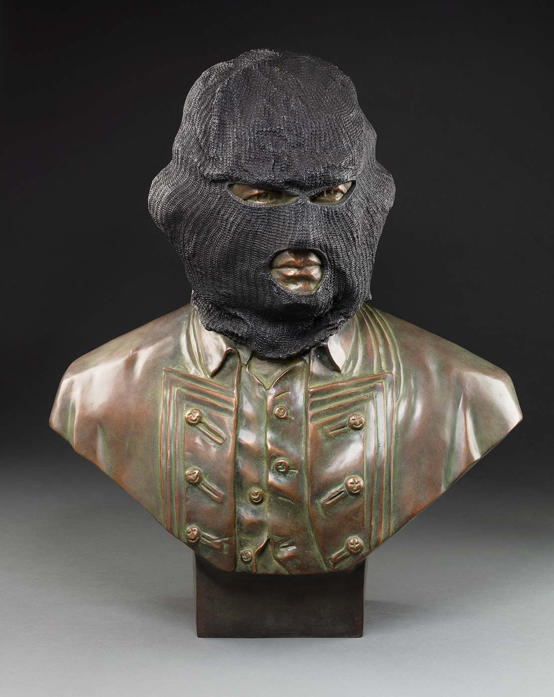 A bronze bust of a males head with a ponytail wearing a dark grey Balaklava.