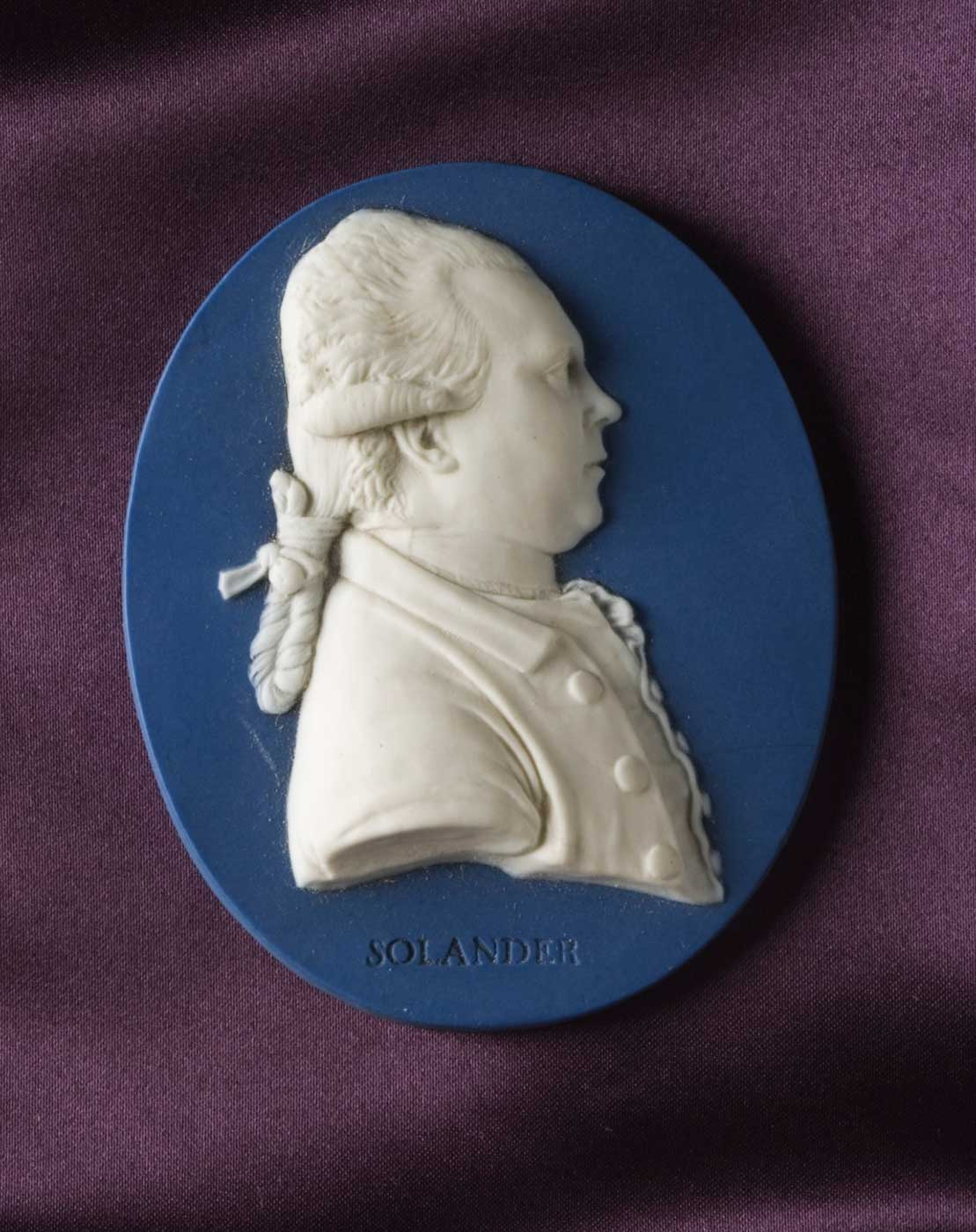 Oval blue jasper medallion decorated with a portrait of Dr Daniel Carl Solander in white jasper, with a stamped impression below the portrait which reads 'SOLANDER'.  - click to view larger image