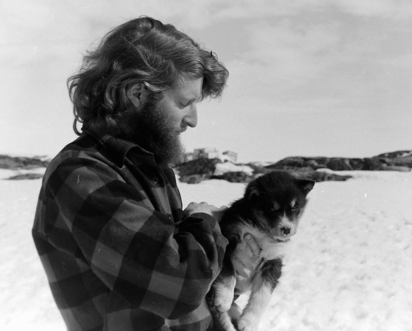 Black and white photograph of a man holding a husky pup.