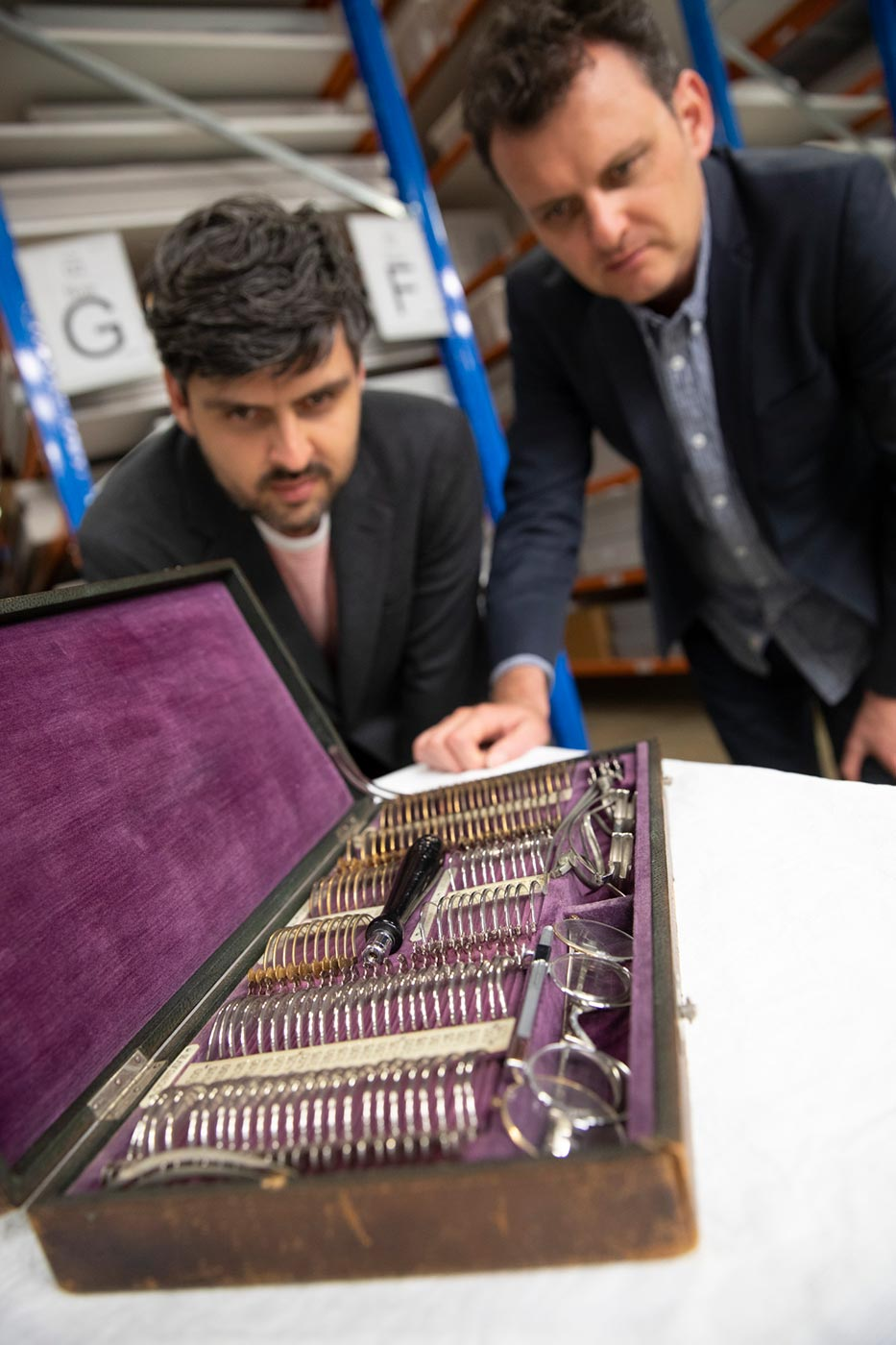 Slava and Leonard Grigoryan inspect a velvet-lined wooden case containing various optical tools. - click to view larger image