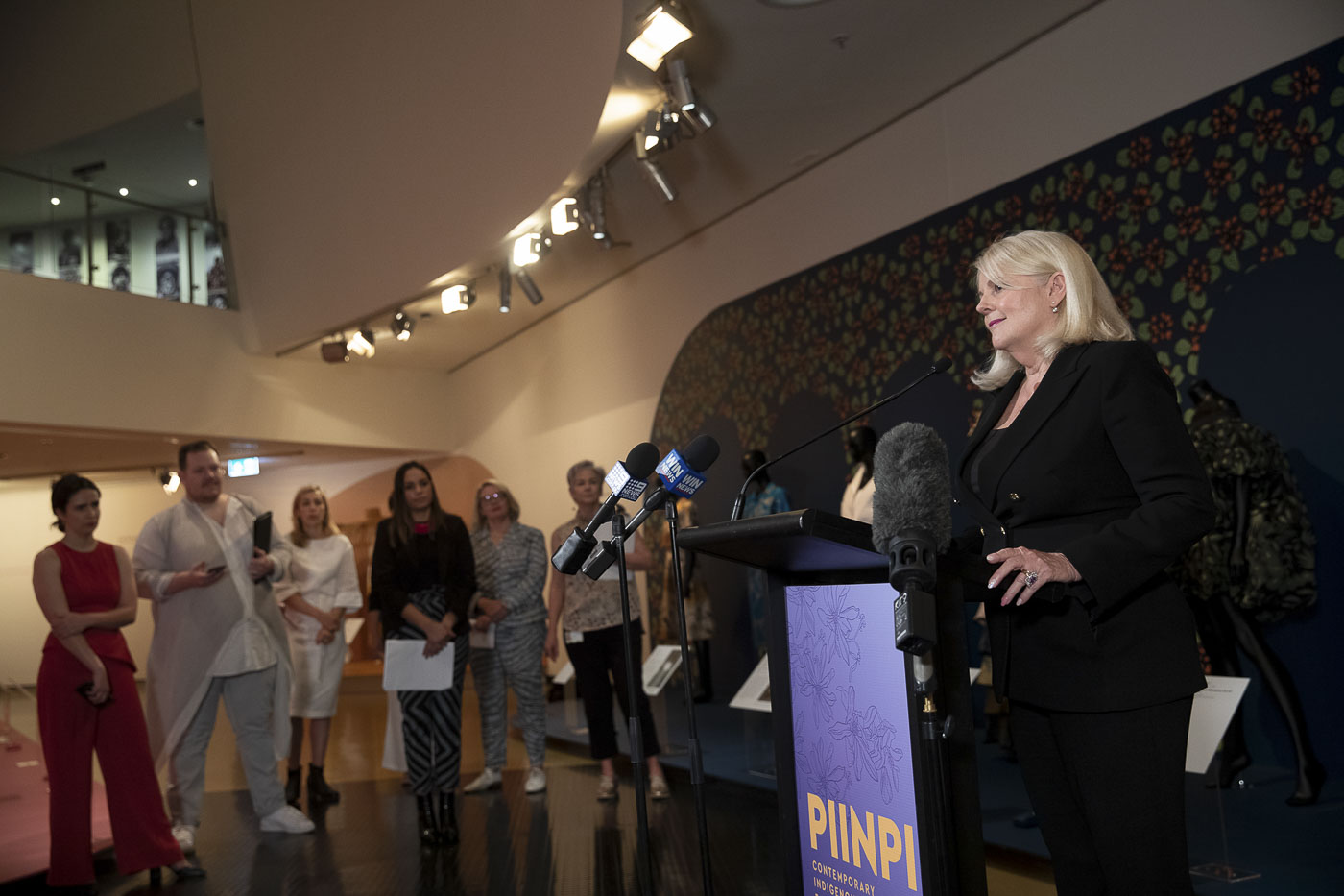 A woman in a formal black suit stands at a podium in front of a decorative exhibition wall. She is addressing an audience for the opening of a fashion exhibition. - click to view larger image