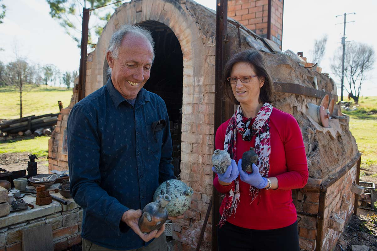 A man and a woman holding remnants of ceramic vessels in front of a kiln. - click to view larger image