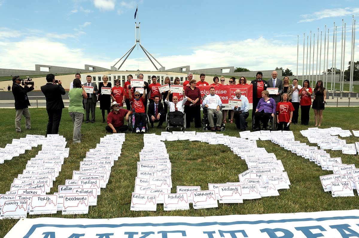 A group of campaigners and the media are gathered on the lawns of Parliament House in Canberra. The campaigners, some in wheel chairs, are holding up placards. Signs with cities, towns and districts across Australia in the formation of NDIS lie on the grass in front of them..