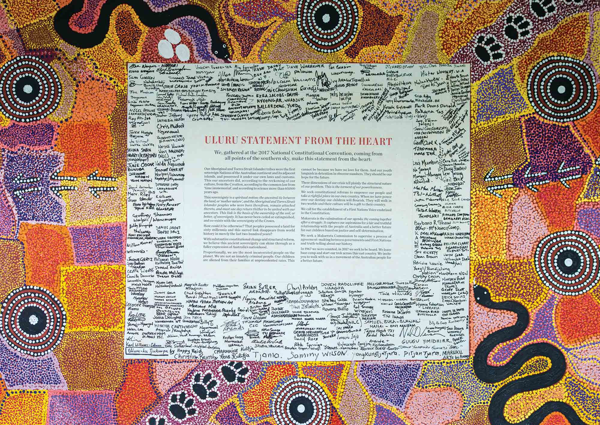 """A statement titled """"ULURU STATEMENT FROM THE HEART"""", surrounded by many signatures, and mounted on a colourful dot painting. - click to view larger image"""