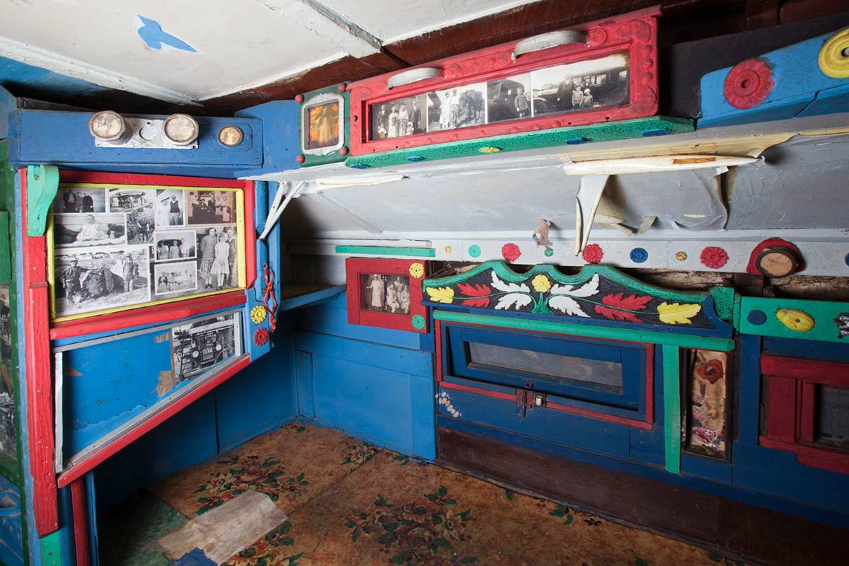 A colour photograph of the interior decorated walls of the Saw Doctor's wagon. - click to view larger image