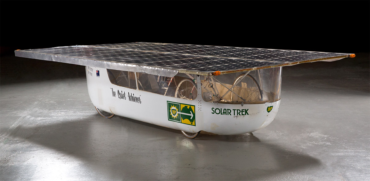 A solar-powered vehicle clad in a white fibreglass, featuring a large flat rectangular array of solar panels mounted on the roof, bicycle fittings including wheels and frame to the interior, and the text